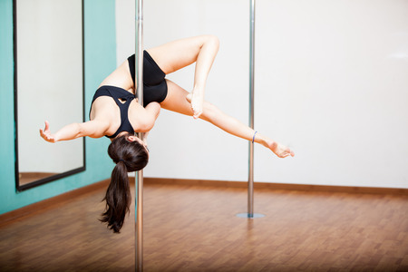 Young brunette trying a beautiful pose during a pole dancing class