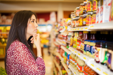 Beautiful brunette looking at some shelves in a supermarket trying to decide what to buy