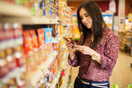 Cute young woman examining a product label while shopping at the store