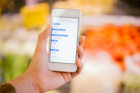 Closeup of a woman s hand holding a smart phone with a shopping list at a grocery store