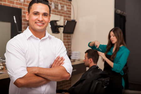 Handsome young barber shop owner smiling and managing his business