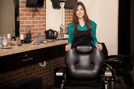 Foto für Gorgeous young woman standing behind a salon chair and greeting customers to her hair salon - Lizenzfreies Bild