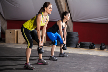Two young women working out in a cross-training gym using kettlebells