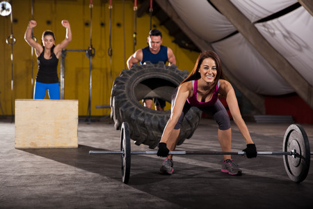 Happy people working out in a cross-training gym using weights, boxes, and tires