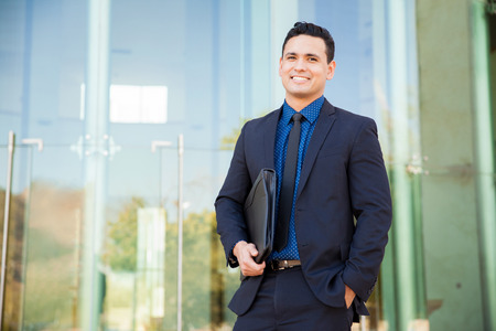 Photo pour Handsome Hispanic man in a suit carrying his resume and waiting for a job interview and smiling - image libre de droit