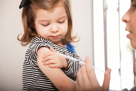 Closeup of a cute little girl getting a flu shot at a doctor