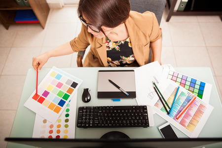 Top view of a young graphic designer working on a desktop computer and using some color swatches