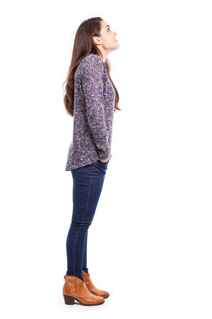 Full length profile view of a young brunette in casual clothing looking up towards copy space