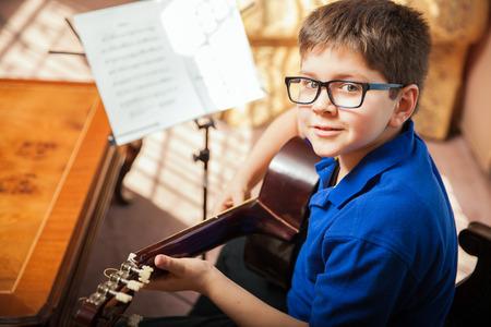 Photo pour Portrait of a young boy with glasses practicing a song during a guitar lesson at home - image libre de droit