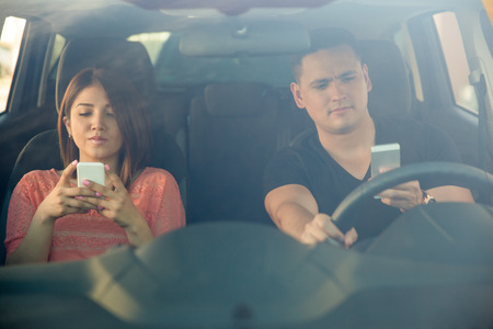 Photo pour Portrait of a young couple texting and driving together, as seen through the windshield - image libre de droit