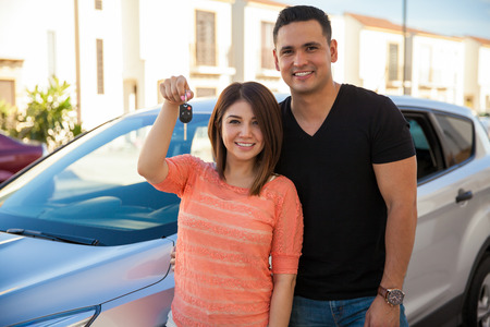 Pretty girl and her husband showing off their car keys for their brand new car