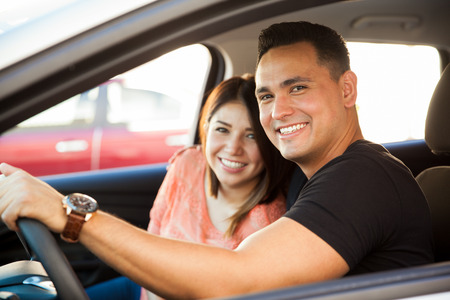 Portrait of an attractive Hispanic couple driving a car and about to go on a trip