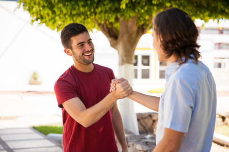 Pair of male friends greeting each other with a handshake at school