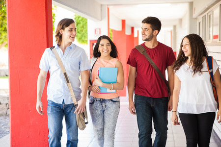 Photo pour Attractive Hispanic college students walking together and talking on a school hallway - image libre de droit