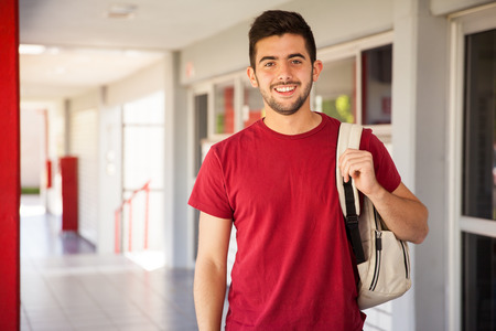 Photo for Portrait of a Hispanic college student carrying a backpack and standing in a school hallway - Royalty Free Image
