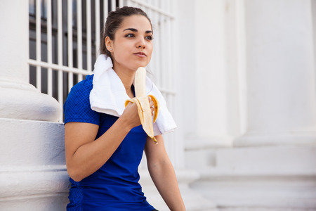 Cute active brunette relaxing after a long workout in the city and eating a banana