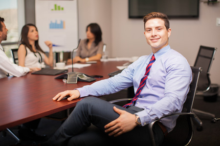 Attractive young lawyer sitting in a meeting room with some of his coworkers and smiling