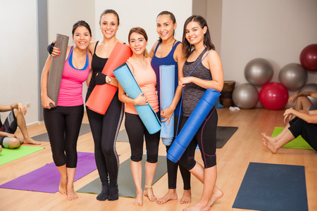 Full length portrait of a group of five women with exercise mats in a yoga studio