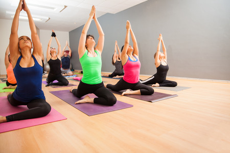 Portrait of a large group of people doing a low lunge pose during a real yoga class