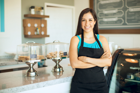 Cute Hispanic female business owner standing in front of her cake shop and smiling