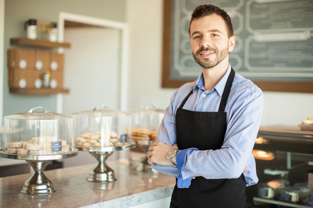 Portrait of a young business owner wearing an apron and standing in front of his cake shop