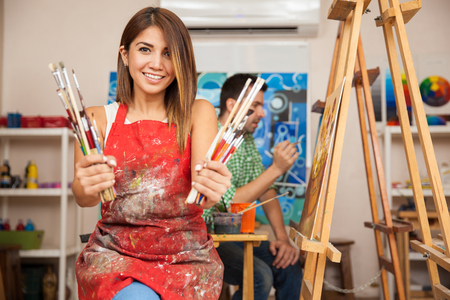 Photo pour Portrait of a gorgeous young brunette wearing an apron and holding a bunch of paintbrushes in an art class - image libre de droit