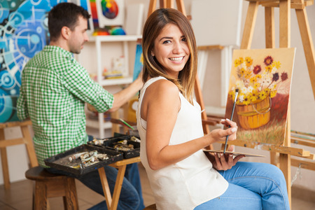 Photo for Beautiful young Hispanic woman and a handsome man attending a painting workshop together and having fun - Royalty Free Image