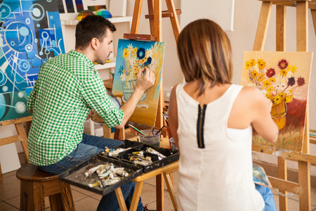 Photo for Rear view of a couple of young adults working on their own paintings while studying at an art school - Royalty Free Image
