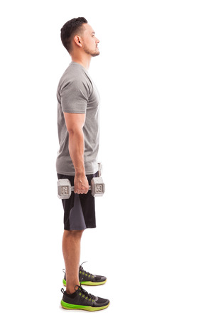 Profile view of a young man in sporty outfit about to lift some weights on a white background