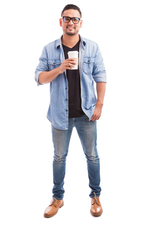Portrait of a young hipster man wearing glasses and drinking coffee from a cup in a white background
