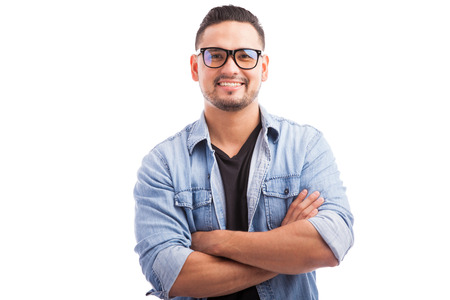 Latin hipster guy wearing glasses with his arms crossed and smiling on a white background