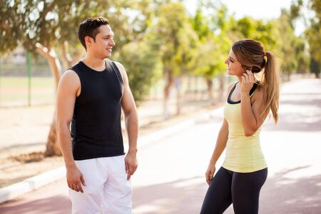 Young Latin man talking and flirting with a girl while both exercise in a running track