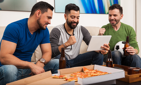 Male friends drinking beer and eating pizza while watching a soccer game on a tablet computer