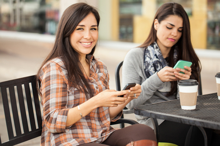Cute young Hispanic brunette using her smartphone and smiling while having coffee with some friends