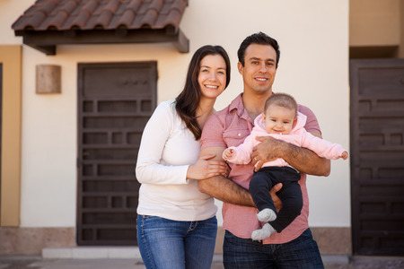 Photo pour Portrait of an attractive Hispanic young couple and their baby girl standing in front of their new home and smiling - image libre de droit