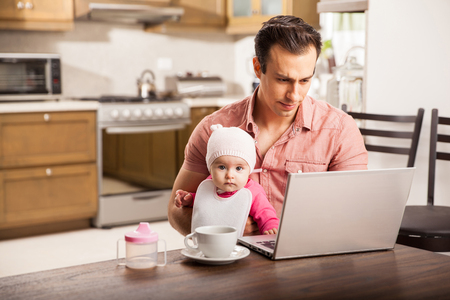 Photo for Attractive young single dad working on a laptop computer at home while taking care of his baby daughter - Royalty Free Image