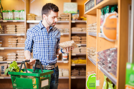 Attractive man with a beard reading a product label while buying groceries at a store