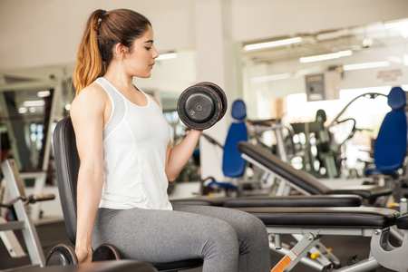 Cute young woman lifting a couple of dumbbells and working on her arms at the gym
