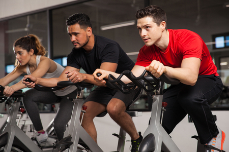 Photo pour Group of three friends doing some cardio on a bicycle at a gym and concentration on their workout - image libre de droit