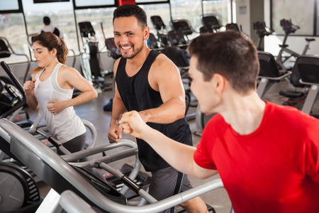 Happy young men bumping their fists while doing some jogging on a treadmill at the gym