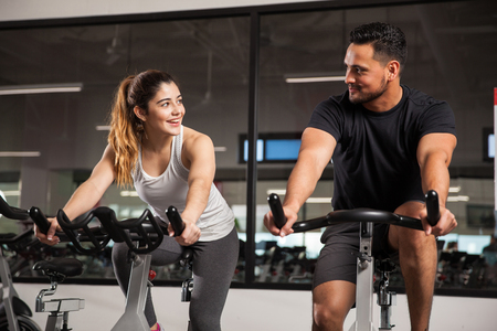 Foto de Beautiful young Hispanic woman flirting and talking to a guy while they both do some spinning at a gym - Imagen libre de derechos