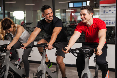 Portrait of a couple of young men talking and laughing while doing some spinning at a gym