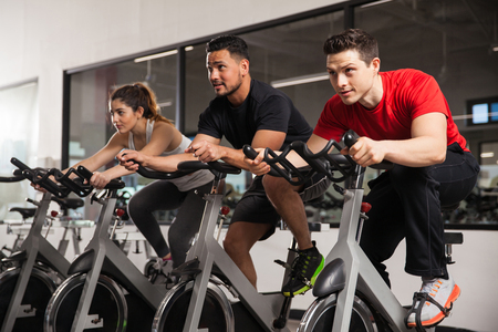 Photo pour Three young people doing some cardio and acting all focused during their spinning class - image libre de droit