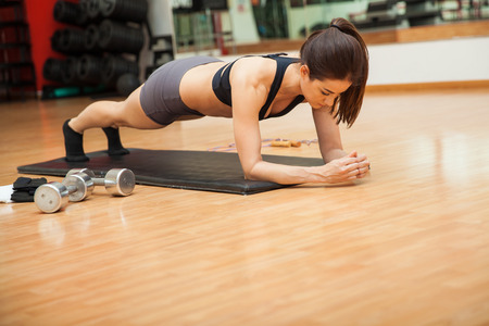 Foto de Athletic young woman holding a plank pose and working on her abs at the gym - Imagen libre de derechos