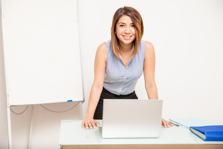 Photo pour Cute young woman leaning on a desk with a laptop computer and standing next to a flip chart - image libre de droit
