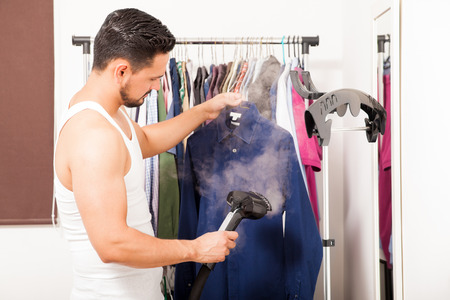 Profile view of a good looking young man using a steamer on a shirt before getting dressed