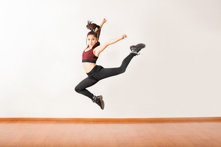 Photo for Portrait of a beautiful female jazz dancer jumping in a dance studio and holding a pose - Royalty Free Image