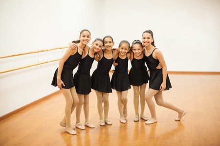 Photo for Full length portrait of a group of Hispanic girls standing together and having fun and smiling during dance class - Royalty Free Image