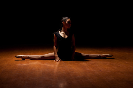Gorgeous young female dancer doing a leg split on the dance floor in the middle of a performance in a dark stage on a spotlight