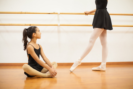 Cute little girl looking up to her dance teacher while she performs a ballet routine next to a barre